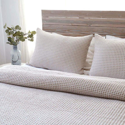 Natural cotton blanket with small waffle weave texture.