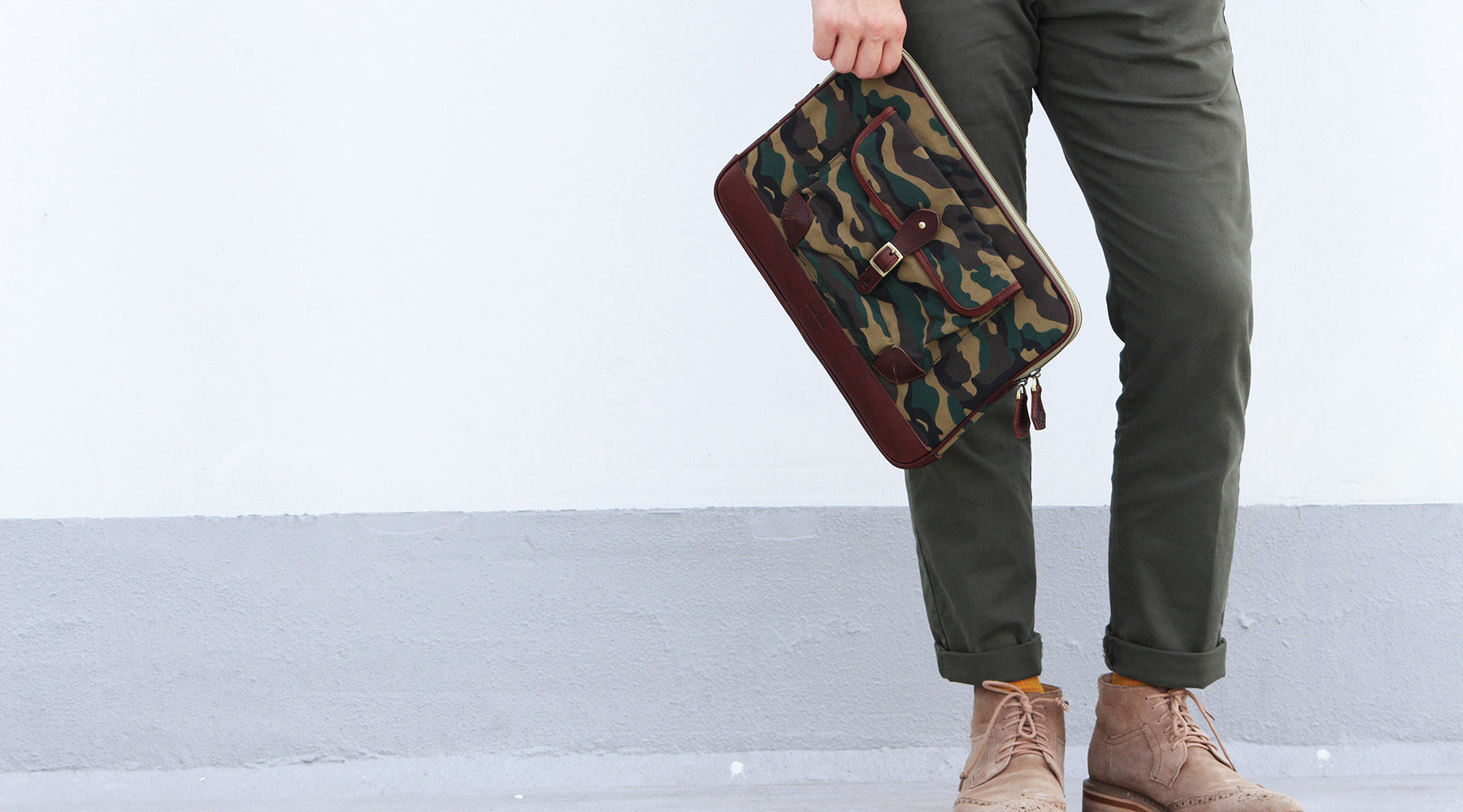 "Our brown full-grain leather Alden Folio with Camouflage canvas delivers a fashion forward option to carrying documents around. Able to fit a 13"" laptop comfortably and crafted with an easy access outer compartment, the Alden is a stylish piece for everyd"
