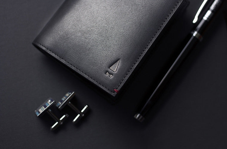 The Birch Cardholder made of Onyx Black full-grain leather, a timeless shade accented with detailed red threading for the modern gentleman.