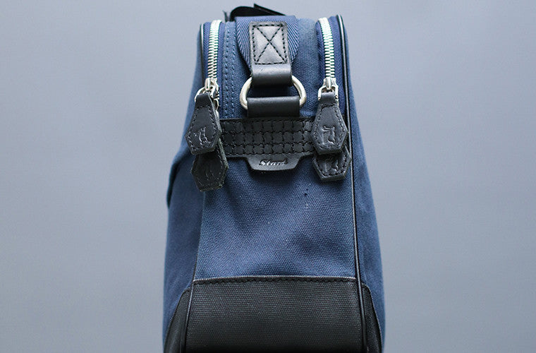 The Thyme is your classic messenger in Space Blue, contrived of full-grain leather, waxed canvas, YKK Japan zippers and tech-friendly slots. While holding all your essentials in a compact profile, it speaks volumes through understated detailing and finish