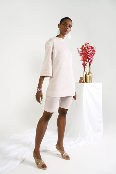Pink bell sleeve tunic with crewneck on model