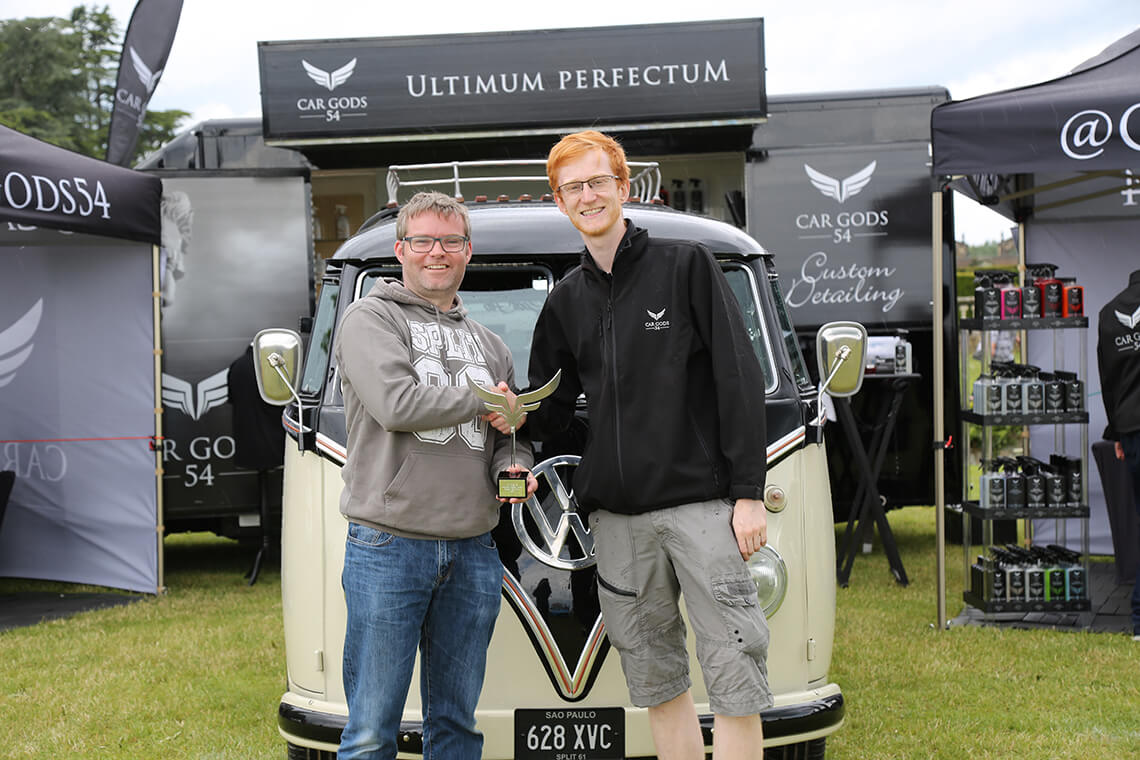 Collecting trophy in front of VW Kombi