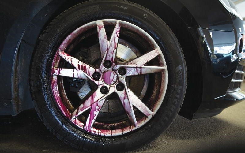 Purple cleaning liquid running down a car wheel