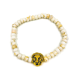 lion head bead strung along with spotted white faceted beads on elastic cord