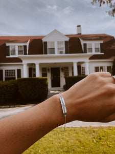 Coordinates bracelet help up in front of house where you grew up in