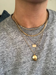 Yantra necklace layered with other gold necklaces