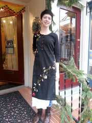 model in double layered boho chic tunic dress black, with embroidered red roses vine, standing on porch.