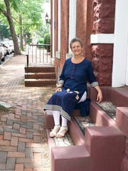 model seated on red brick steps, wearing a long tunic navy, linen fabric with embroidered white lotus flowers and white trim paired with white leggings.