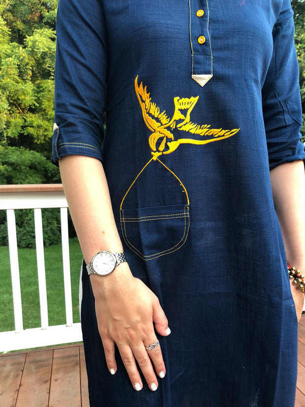 close up of yellow bird embroidery on long tunic navy, linen fabric, 3/4th long sleeves.