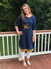 model wearing long tunic navy, linen fabric, with embroidered yellow bird, 3/4th long sleeves, paired with white leggings.