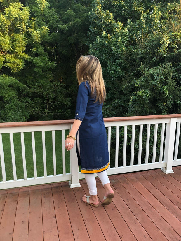 back view of model wearing long tunic navy, linen fabric, with embroidered yellow bird, 3/4th long sleeves, paired with white leggings.