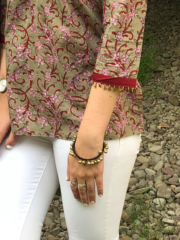 sleeve closeup of cotton boho chic short tunics, block print, fine sequence trim, sported with white denim jeans.