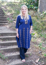front view long linen tunic navy with tribal embroidery on front panel in tan, 3/4th long sleeves paired with navy pants.