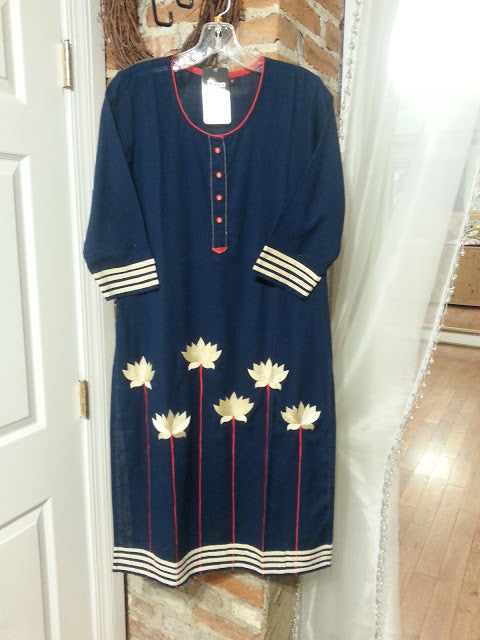 on a hanger a long tunic navy, linen fabric with embroidered white lotus flowers and white trim paired with white leggings.
