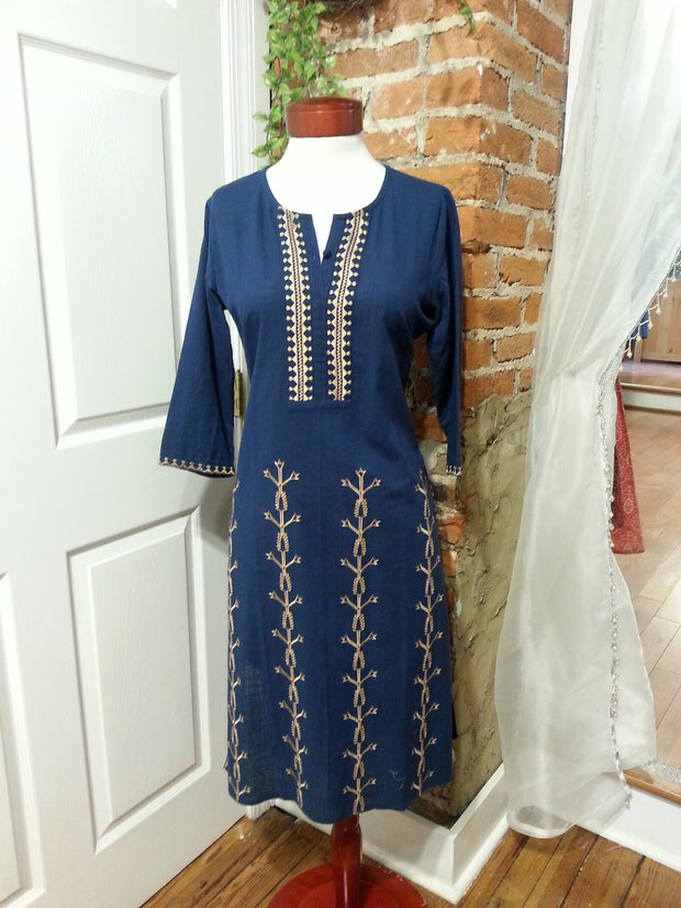 mannequin wearing long linen tunic navy with embroidered front panel in tan, 3/4th long sleeves paired with navy pants.
