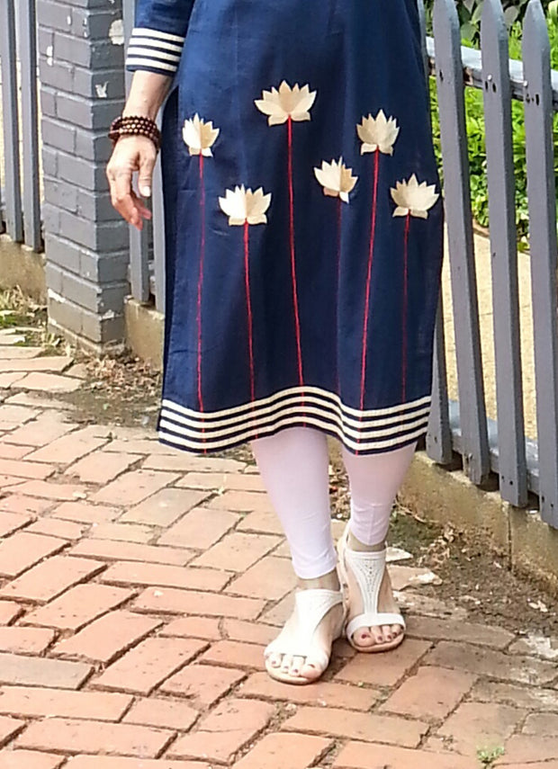 closeup of bottom of long tunic navy, linen fabric with embroidered white lotus flowers and white trim paired with white leggings.