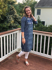 side view of teardrop patch print long cotton tunic navy-white, with 3/4th long sleeves paired with white leggings.