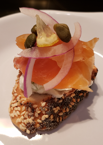 Artisanal Canadian Cold Smoked Atlantic Salmon on top of a round of sesame and poppy seed twisted bagel, with cream cheese, julienne red onion, caper and a tiny triangle of lemon.