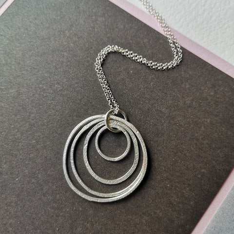 "This beautiful necklace is made up of four silver circles imprinted with a delicate leaf motive, which compliments the double circle earrings also made by jeweller Ami Hallgarth. This would be a perfect present for a nature lover. It hangs 18"" long & comes boxed."