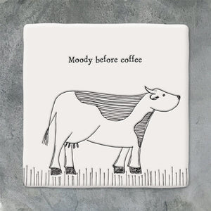 A porcelain keepsake drinks coaster with the words 'Moody before Coffee' and an image of a cow. 10 x 10 x 0.8cm