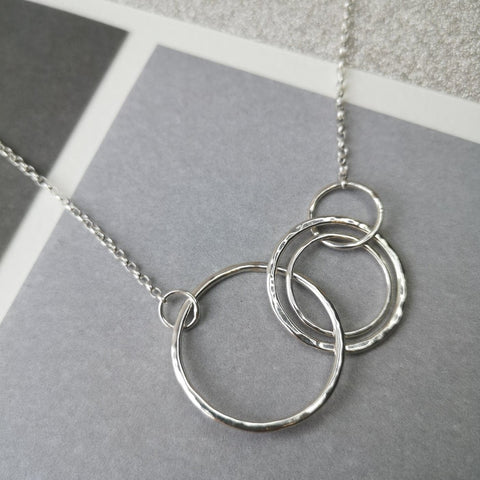"This beautiful silver necklace is made up of four sterling silver hammered rings that are joined but move independently. It would make a lovely gift as the circles could symbolised many things - decades, children, friends etc or just a gorgeous present! Made by the lovely Halifax based Ami Hallgarth.  It hangs 20"" & comes gift boxed."