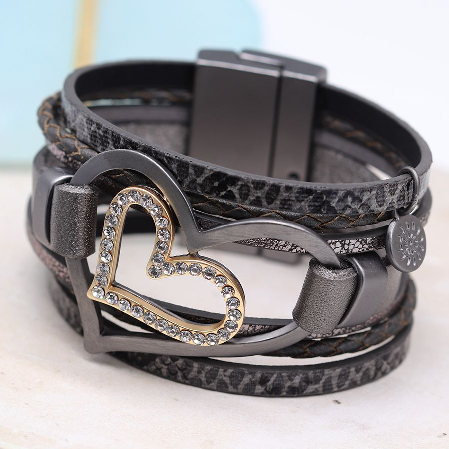 Multi strand leather bracelet in dark grey featuring contrasting textures and a large double grey and gold heart with crystal detailing.