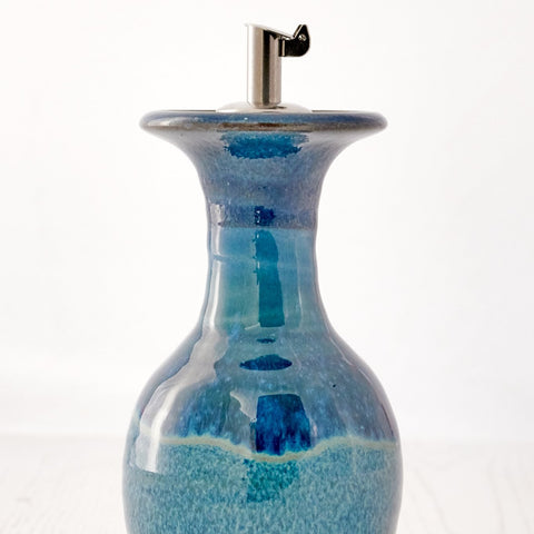 An Olive Oil Decanter, just short of 13cm in height. Perfect for drizzling over salads, with a stainless steel flip top pourer. Holds approximately 150ml. Each piece is made on a potters wheel and hand glazed, therefore size and colours may vary slightly. Available in three colours,  Highland Heather Aqua Marine Sand bay  Come complete with gift box