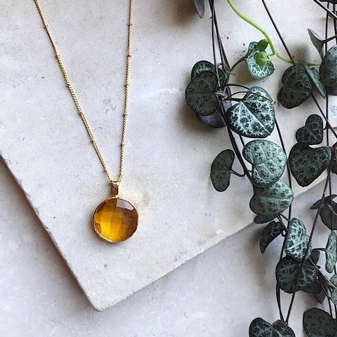 The Sofia Necklace is a chic and elegant minimal necklace formed of a circular pendant  with a Citrine quartz at its centre.   Metal is 22 carat gold on sterling silver.   Chain measures 22 inches.   All jewellery comes boxed.