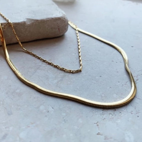 This stunning 20 inch flat snake chain is made up of gold plate on sterling silver. This is an extremely elegant and minimal style that is perfect for every day wear. The snake chain has a flattened effect.   A staple must have in all women's necklace collections, our top pick. Layer it up with other necklaces as shown for the full effect.
