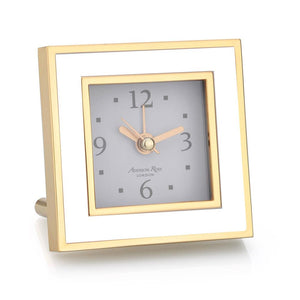 This White Enamel Alarm Clock is finished in gold with a luxury dove grey velvet back. This gorgeous desk or bedside square clock has an alarm and requires a AA battery. The movement is encased within a removable gold cover. The clock comes with 1 screw in leg.  This clock features a silent sweep movement making it the perfect addition to a bedside table.  Measures 8cm x 8cm x 5.5cm (including leg)  This exclusive Addison Ross design is tissue wrapped within one of their beautiful gift boxes.