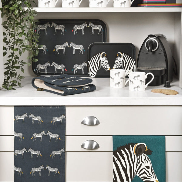 These stylish handmade printed trays feature endangered Grévy's zebras on a navy charcoal background. The small tray has two zebras which are patterned with distinctive black and white stripes and bursts of mustard yellow. Whilst the large tray has a repeated pattern with hints of mustard yellow, pink and blue.   These practical trays are perfect for summer parties and are made from FSC certified Birchwood.  FSC Certified Birchwood Available in two sizes:- Small: 27cm x 20cm Large: 43cm x 33cm Handmade