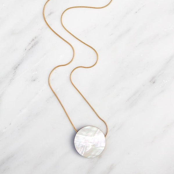 Sophisticated pendant necklace with composition of beads made from wood, brass, and Mother of Pearl veneer.  Collection No.9 combines unexpected materials with simple forms and movement. Playful and bold with eye-catching statement pieces and elevated essentials.  Handmade in North London.