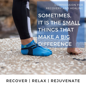 ZaTech® Compression Socks. A woman bending down stretching wearing a pair of blue Low Cut Edition compression socks on a cliff over an ocean bay. Text reads Sometimes the small things make a big difference. Recover | Relax | Rejuvenate