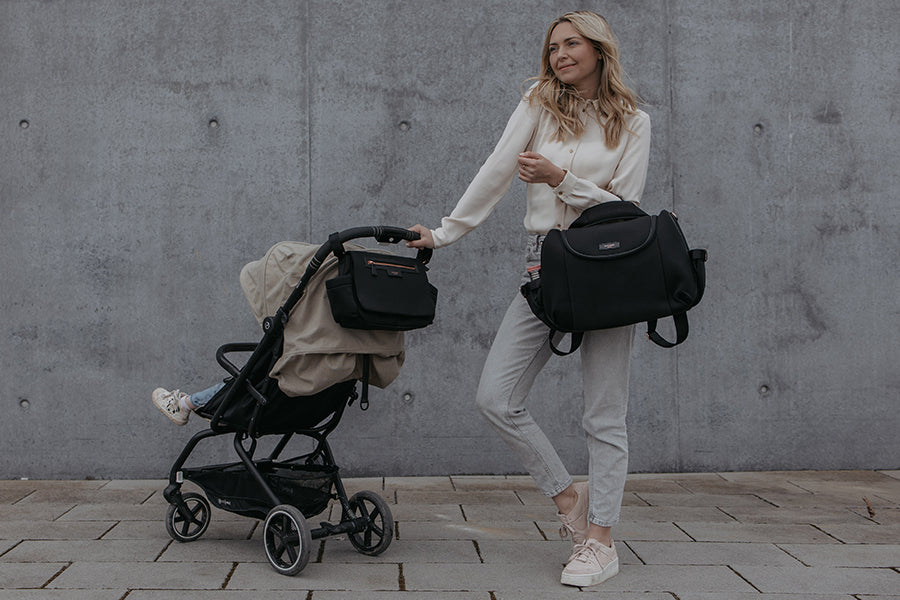 Mum out with her stroller organiser luxe black on the stroller with the baby. She is also carrying her Poppy Luxe black changing bag as a convertible bag over her shoulder.