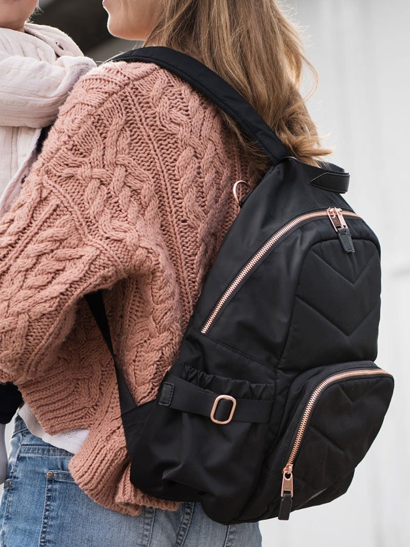 storksak hero quilt black, changing bag backpack, in quilted nylon with rose gold hardware, side view of mum wearing bag and holding baby