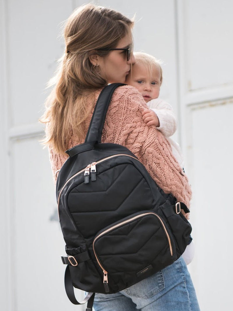 storksak hero quilt black, changing bag backpack, in quilted nylon with rose gold hardware, mum wearing bag and holding baby