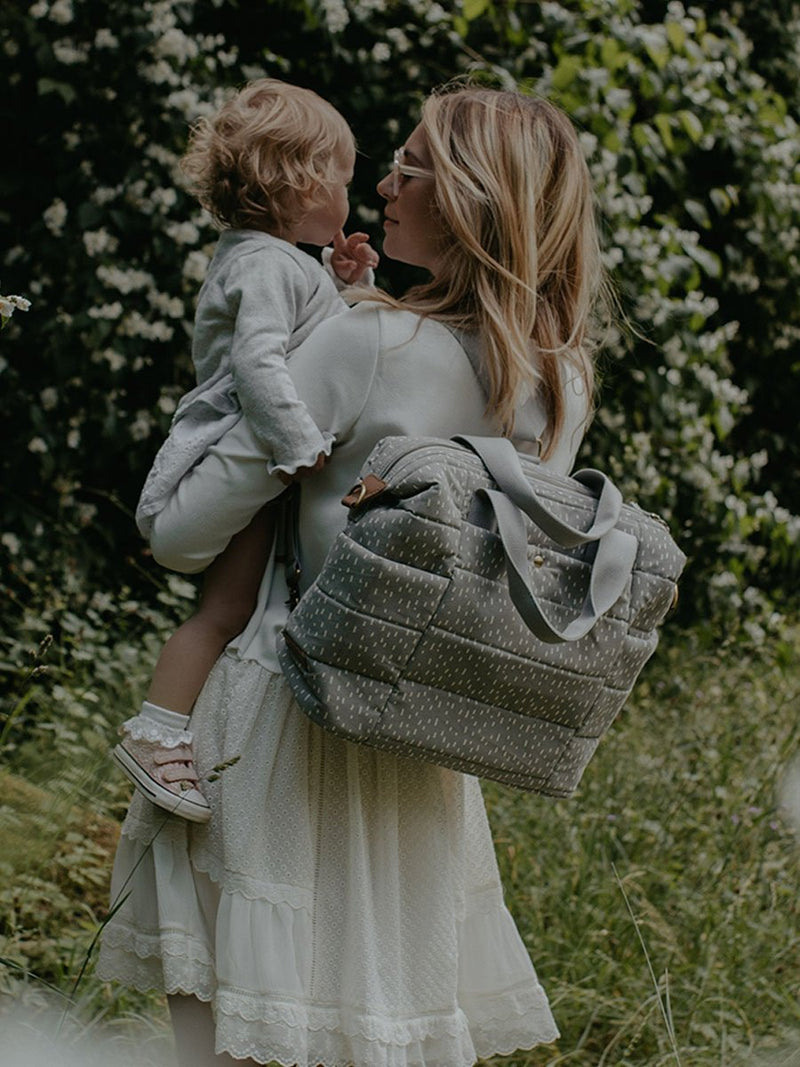 storksak organic cotton tote grey raindot, mum wearing as backpack and holding baby