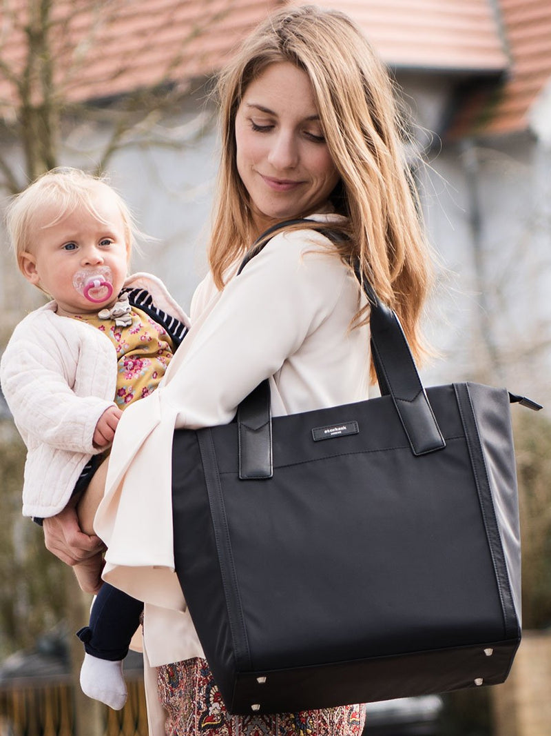 Storksak Eliza Black Changing Bag, tote shape, mum carrying bag and holding baby