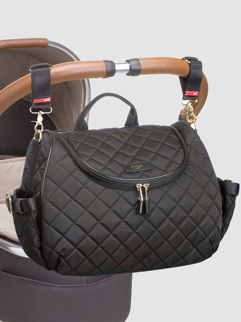 storksak poppy quilt black, convertible changing bag, attached to pram with stroller clips