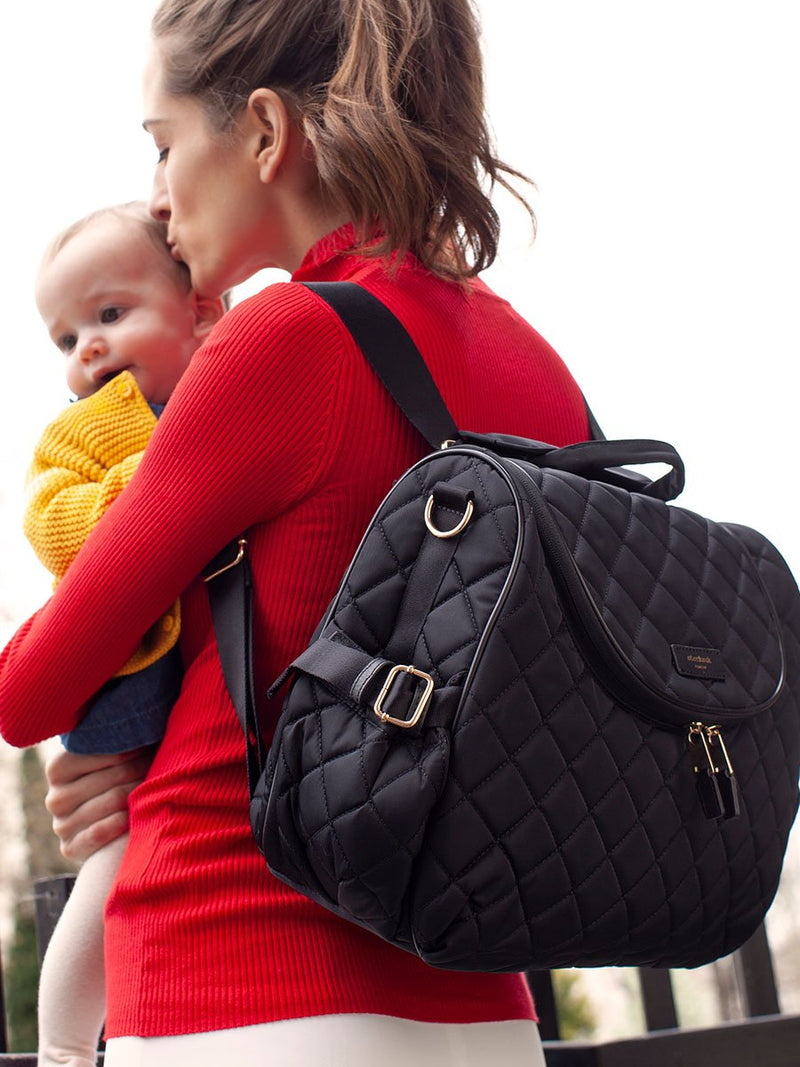 storksak poppy quilt black, convertible changing bag, mum wearing bag as backpack and holding baby