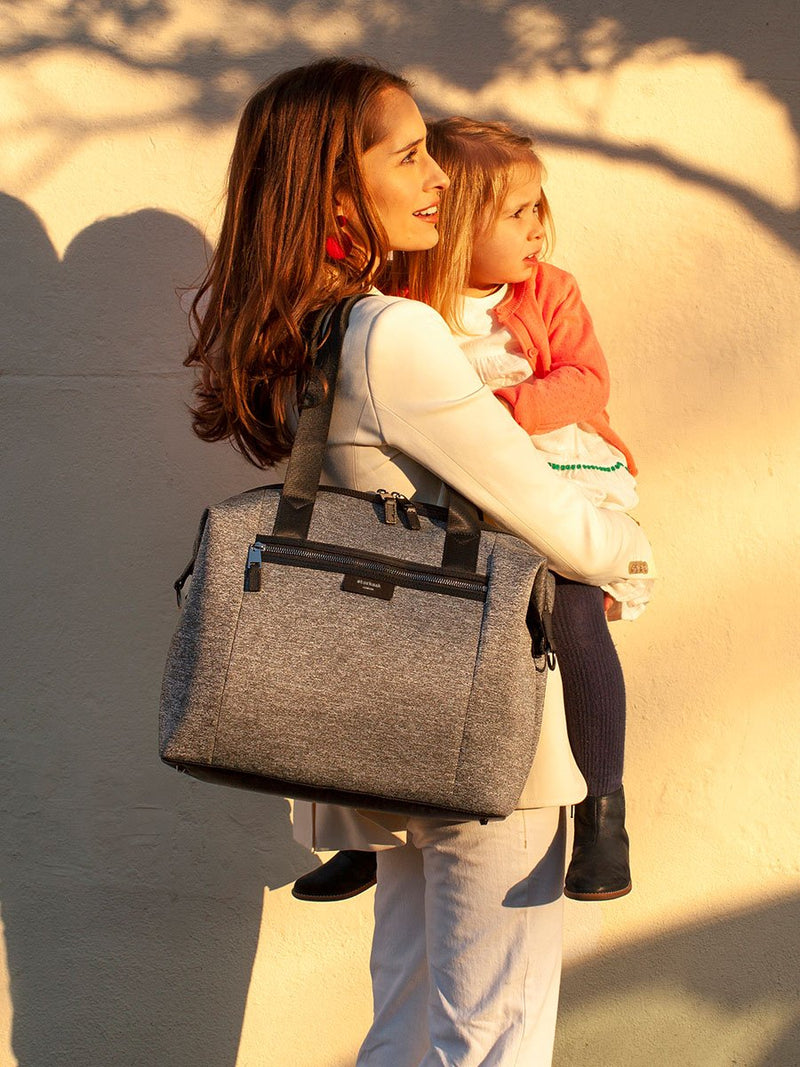 Lifestyle storksak stevie luxe scuba grey marl, changing bag, mum carrying bag and holding child