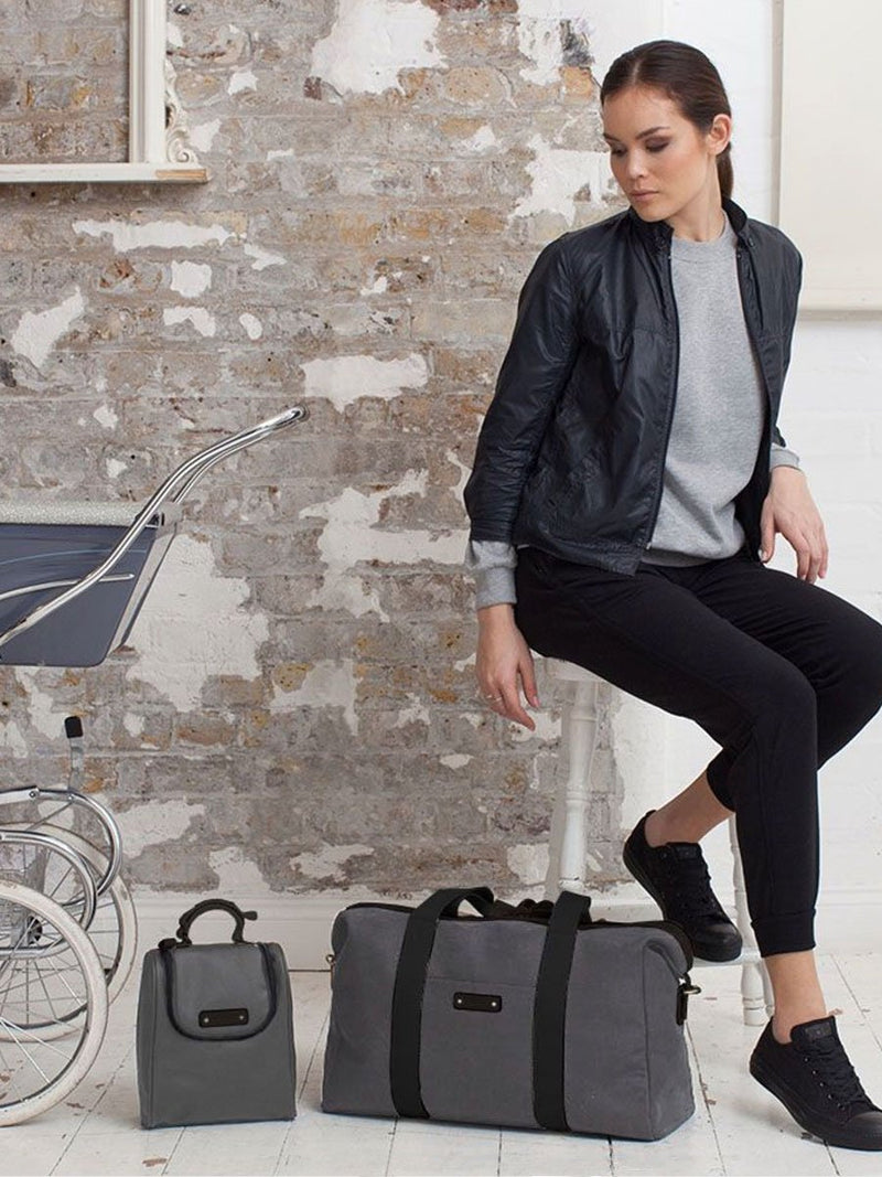 Lifestyle storksak bailey charcoal, hospital & weekend bag, model with bag next to pram