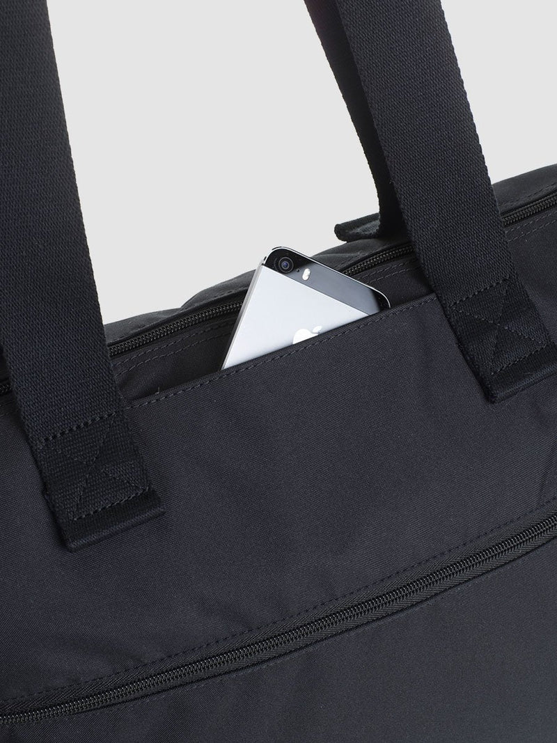 storksak travel expandable tote black, changing bag, close up of front slip pocket
