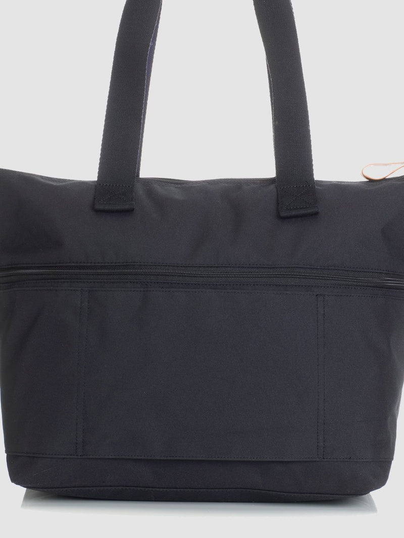 storksak travel expandable tote black, changing bag, back view showing luggage handle slot