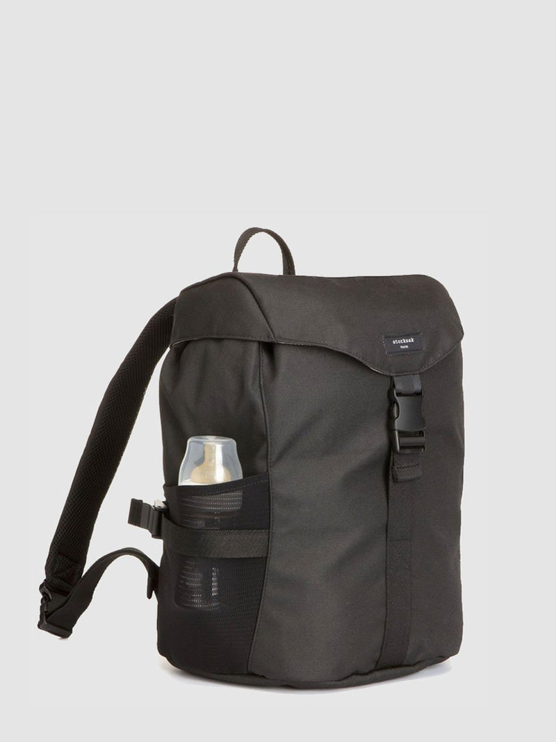 storksak travel eco backpack black, changing bag rucksack, recycled material, front view with baby bottle in side pocket