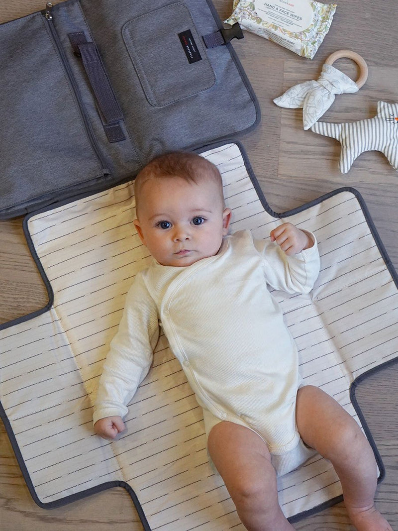 storksak travel change station grey, baby lying on changing mat