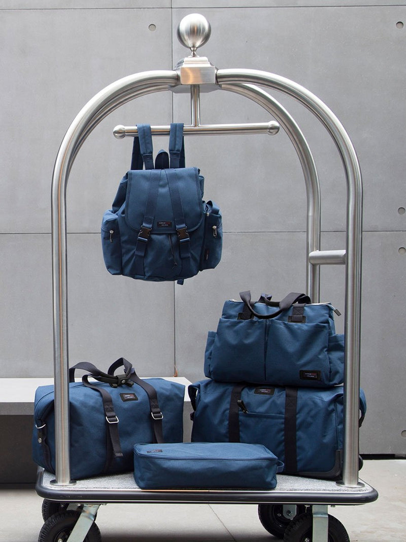 storksak travel shoulder bag navy, 3 compartments changing bag, on hotel trolley with other bags