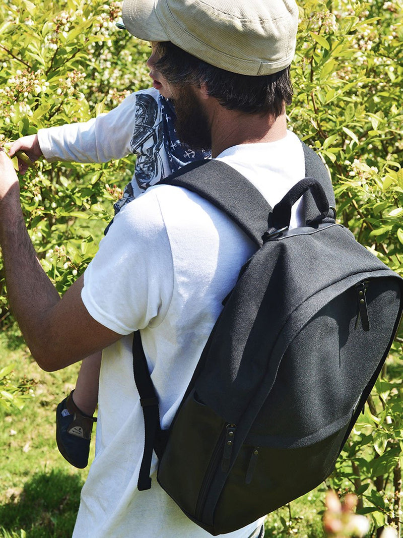 storksak taylor charcoal backpack changing bag, dad wearing bag and carrying child