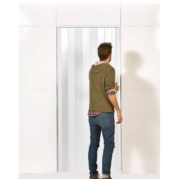 Man opening blinds on door in L shaped everpanel L shaped wall door kit
