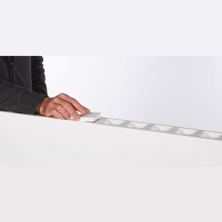man putting can on white l shaped wall partition divider
